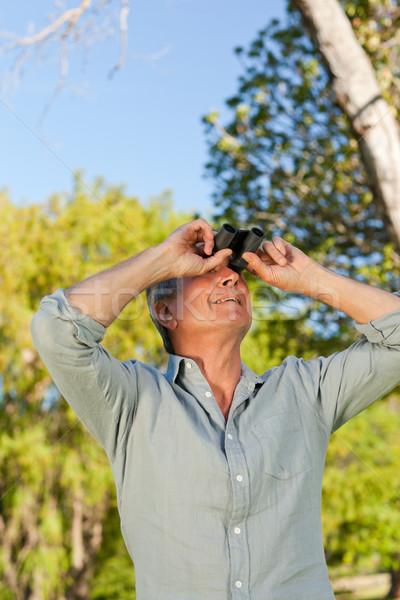 Senior man looking at the sky with his binoculars Stock photo © wavebreak_media