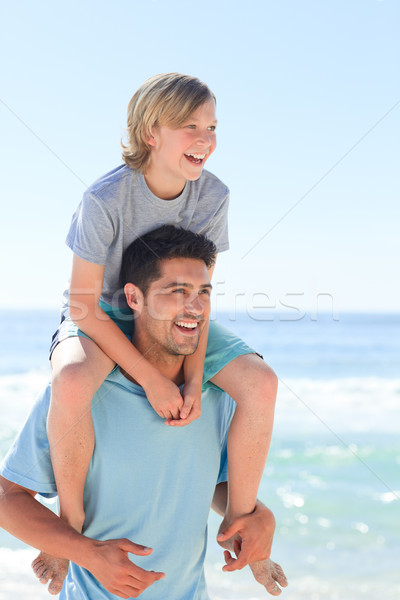 Father having his son a piggyback at the beach Stock photo © wavebreak_media