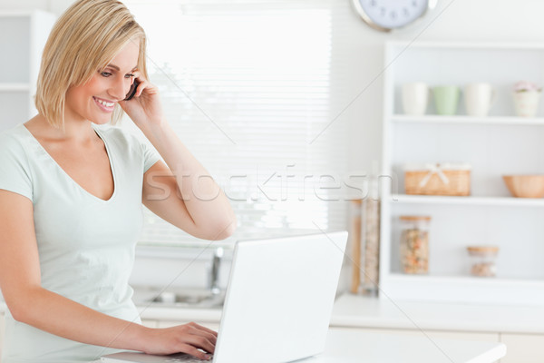Woman with a laptop and a phone searching on the internet in the kitchen Stock photo © wavebreak_media