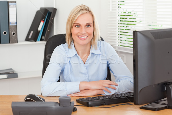 Smiling woman sitting behind a desk in an office Stock photo © wavebreak_media