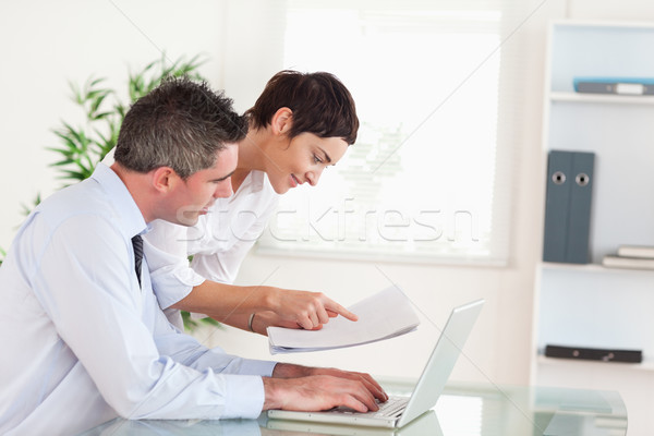 Coworkers comparing a blueprint folder to an electronic one in an office Stock photo © wavebreak_media