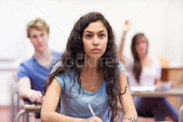 Student listening to her teacher in a classroom Stock photo © wavebreak_media