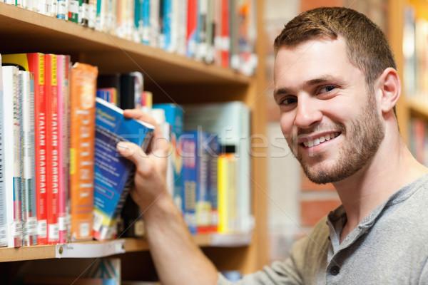 Souriant Homme étudiant livre bibliothèque Photo stock © wavebreak_media