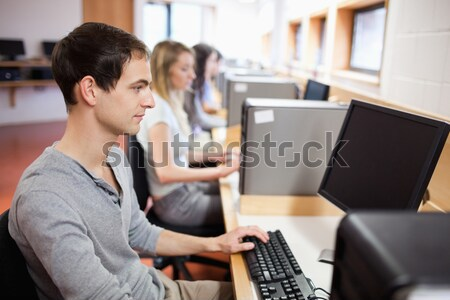 Stock photo: Smiling male student posing with a computer in an IT room