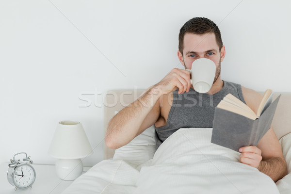 Man reading a novel while holding a cup of coffee in his bedroom Stock photo © wavebreak_media