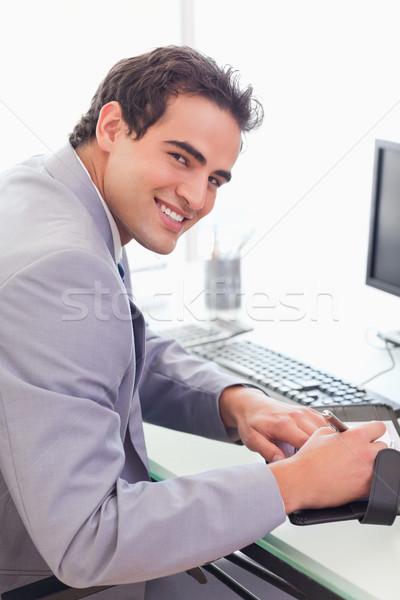 Young businessman writing into his pocket calender Stock photo © wavebreak_media