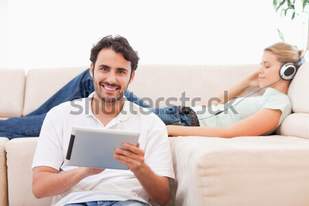 Man using a tablet computer while his girlfriend is listening to music in their living room Stock photo © wavebreak_media