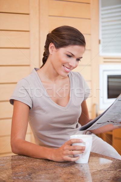 Stok fotoğraf: Gülen · genç · kadın · okuma · gazete · mutfak · ev