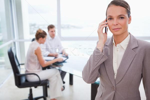Tanácsadó áll mobiltelefon ül vásárlók mögött Stock fotó © wavebreak_media