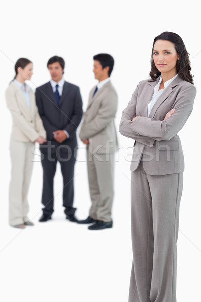 Serious saleswoman with arms crossed and team behind her against a white background Stock photo © wavebreak_media