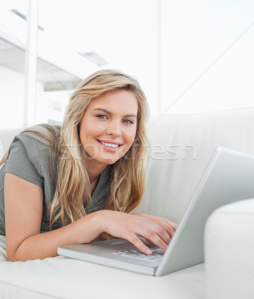 Woman lying on the couch, using her laptop as she smiles and looks forward. Stock photo © wavebreak_media