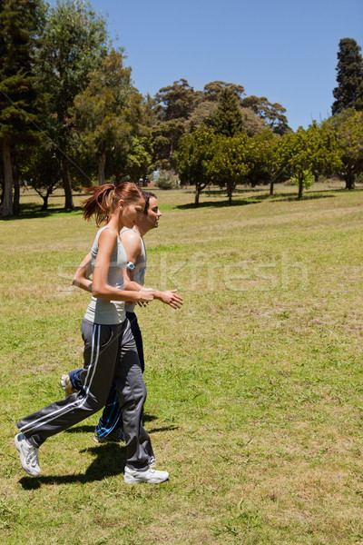 Two friends jogging along side by side other across grass with a view of trees and the sky in the ba Stock photo © wavebreak_media