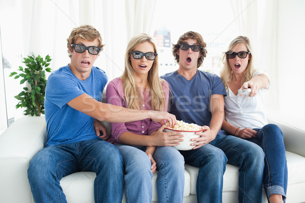 A scared group of people watching a 3d movie while eating popcorn  Stock photo © wavebreak_media