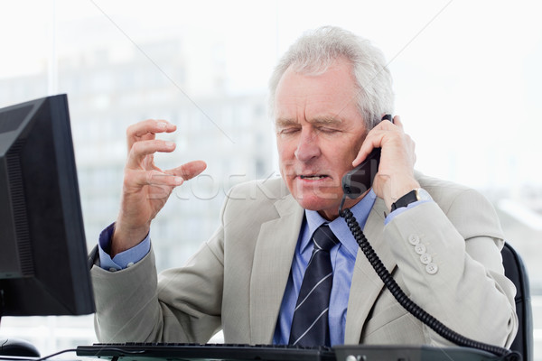 Irritato senior manager telefono ufficio computer Foto d'archivio © wavebreak_media