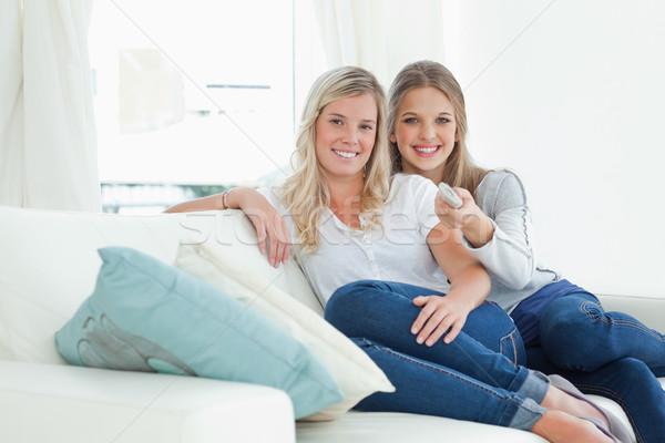 Pár nővérek néz kamera nevetés távirányító Stock fotó © wavebreak_media