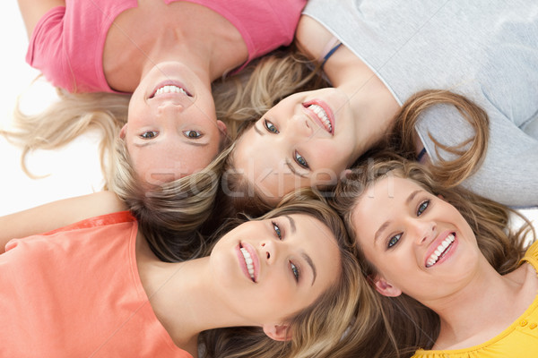 Four smiling girls lying on the ground together with their heads beside one another Stock photo © wavebreak_media