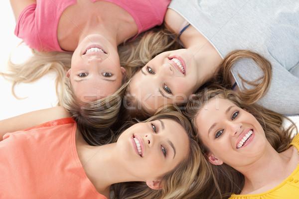 Quattro sorridere ragazze terra insieme accanto Foto d'archivio © wavebreak_media