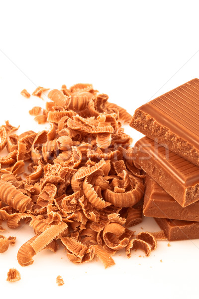 Many chocolate shavings beside a pile of chocolate against a white background Stock photo © wavebreak_media