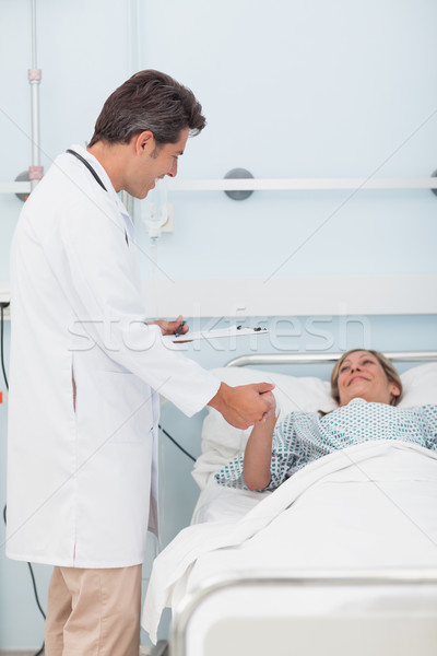Doctor talking to his patient while holding her hand in hospital ward Stock photo © wavebreak_media