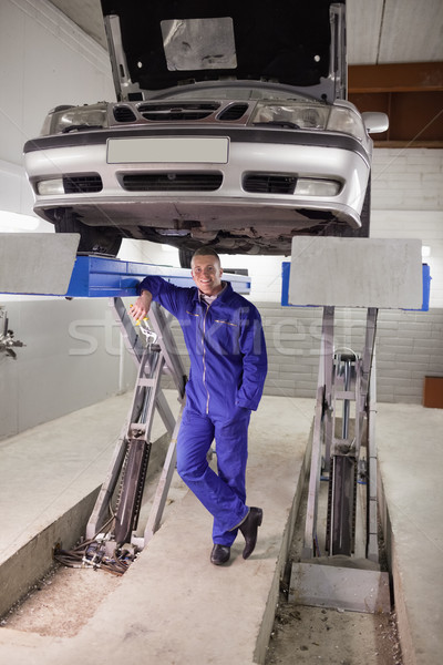 Smiling man leaning on a machine in a garage Stock photo © wavebreak_media