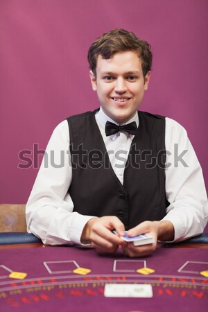 Dealer sitting at table in a casino while shuffling deck of cards Stock photo © wavebreak_media