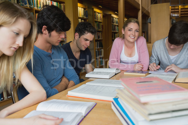 Students in the library studying together around table with one girl looking up and smiling Stock photo © wavebreak_media