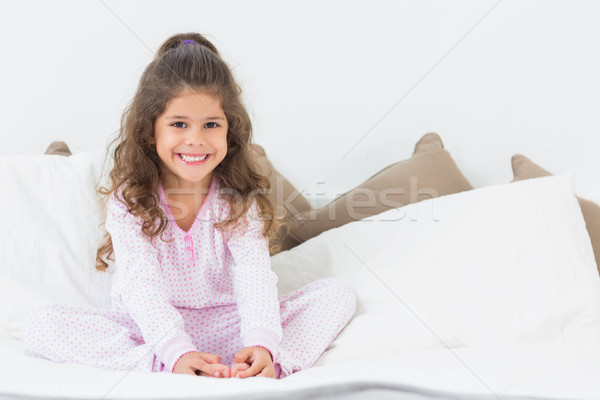 Stock photo: Cute girl sitting on bed