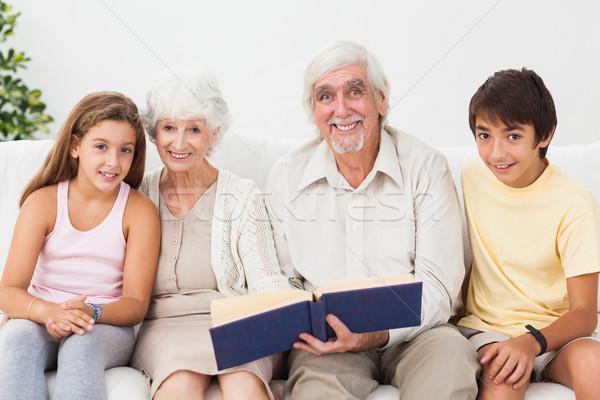 улыбаясь дедушка и бабушка внучата чтение книга диване Сток-фото © wavebreak_media