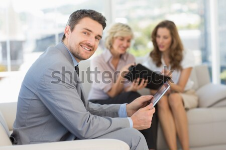 Businessman using digital tablet with colleagues at home Stock photo © wavebreak_media