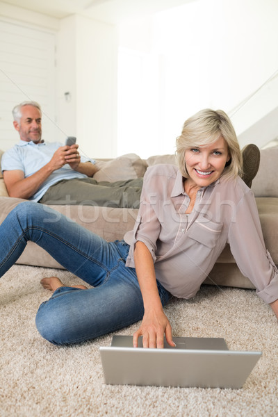 Couple with laptop and cellphone in living room at home Stock photo © wavebreak_media