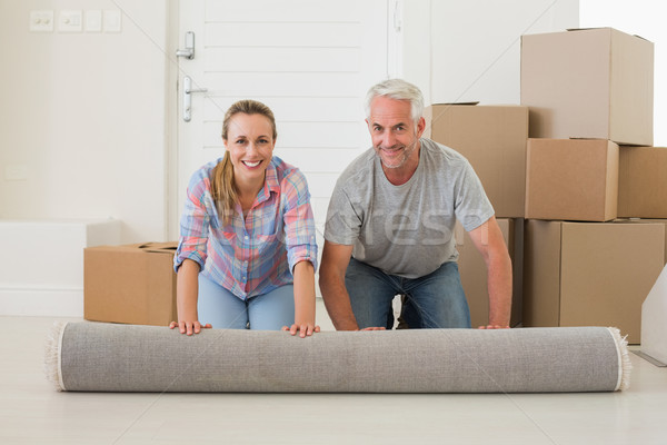 Happy couple rolling out new rug Stock photo © wavebreak_media