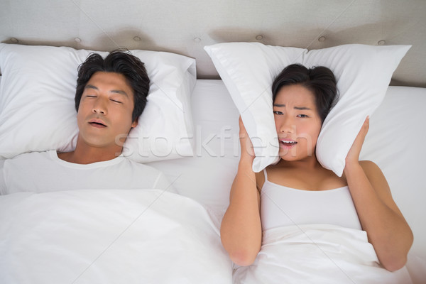 Annoyed woman covering her ears with pillows to block out snorin Stock photo © wavebreak_media