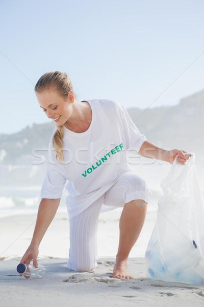 Blonde volunteer picking up trash on the beach Stock photo © wavebreak_media