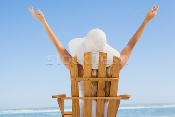 Woman sitting in deck chair at the beach with arms up Stock photo © wavebreak_media