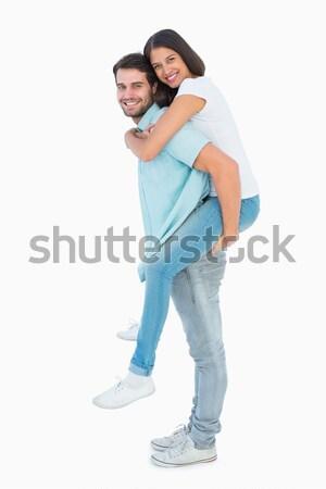 Happy casual man giving pretty girlfriend piggy back Stock photo © wavebreak_media