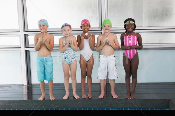 Cute little kids standing poolside with medals Stock photo © wavebreak_media