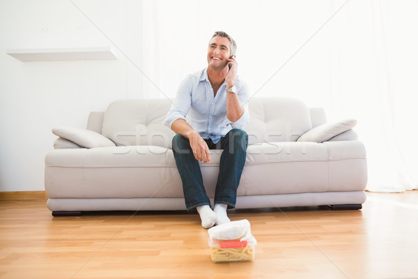 Smiling man phoning on the couch Stock photo © wavebreak_media