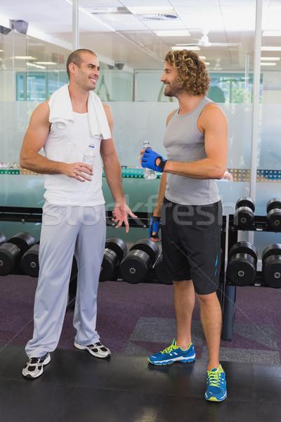 Smiling trainer talking to fit man at gym Stock photo © wavebreak_media