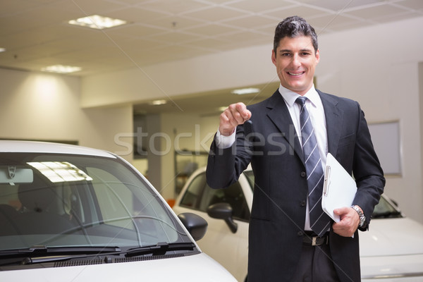 Businessman showing a car key while holding clipboard Stock photo © wavebreak_media