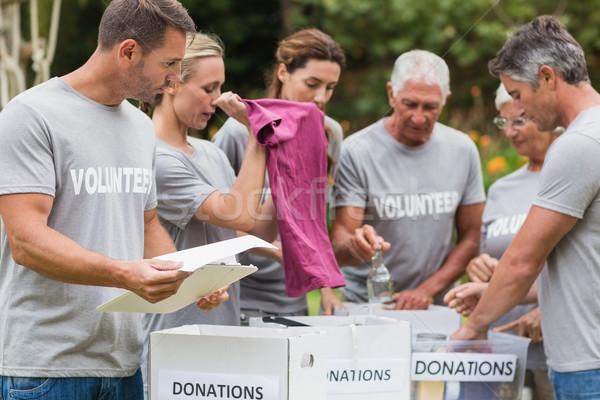 Feliz voluntário olhando doação caixa Foto stock © wavebreak_media