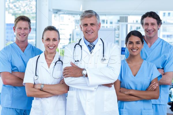 Equipo médicos pie los brazos cruzados sonriendo cámara Foto stock © wavebreak_media