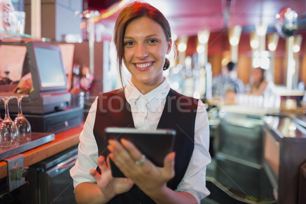 Focused barmaid using touchscreen till  Stock photo © wavebreak_media
