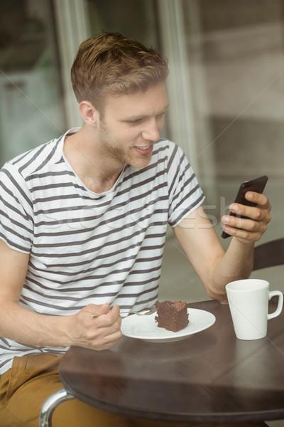 Mosolyog diák csokoládés sütemény okostelefon kávézó egyetem Stock fotó © wavebreak_media