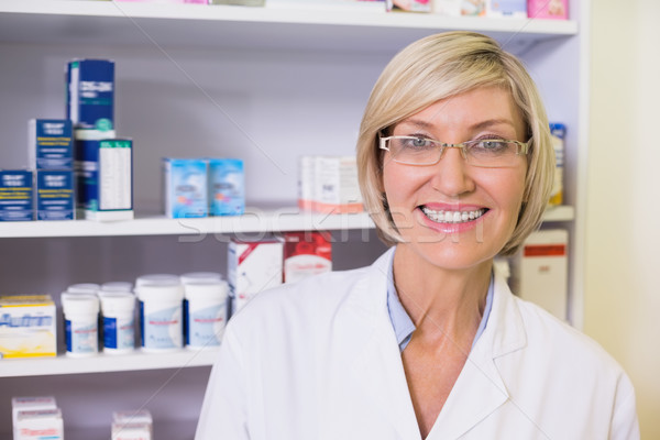 Smiling pharmacist in lab coat looking at camera Stock photo © wavebreak_media