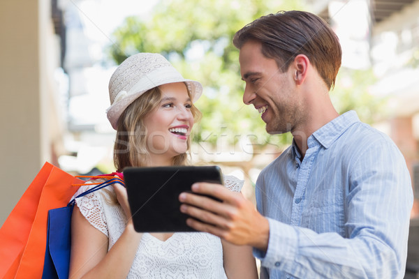 Cute smiling couple looking a tablet Stock photo © wavebreak_media