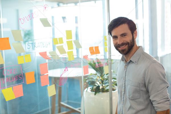Portret uśmiechnięty biznesmen stałego przyczepny zauważa Zdjęcia stock © wavebreak_media