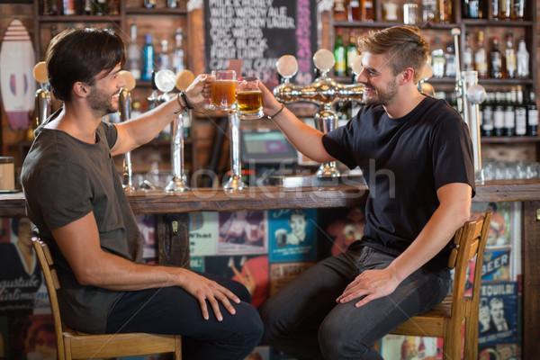 Happy male friends toasting beer mugs in bar Stock photo © wavebreak_media