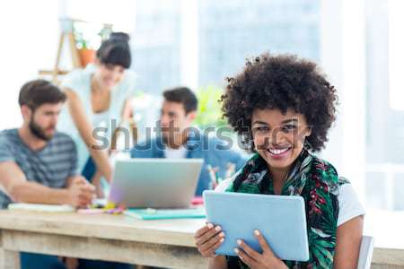 Portrait of smiling waitress with notepad while friends interacting in background Stock photo © wavebreak_media