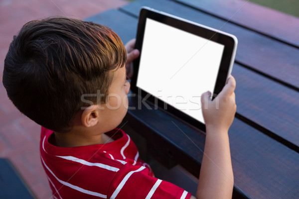 Stock photo: High angle view of boy using digital tablet while sitting at table