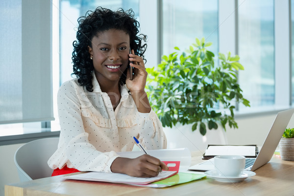 Female executive talking on mobile phone while working at desk in office Stock photo © wavebreak_media